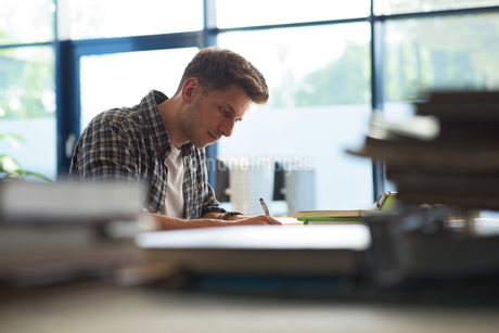Side view of young male student studying at desk in classroomの写真素材 [FYI02239973]