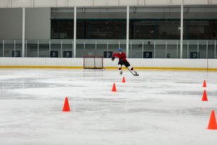 Male ice hockey player practicing drills at rinkの写真素材 [FYI02239976]
