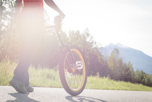 Low section of woman walking with unicycle on roadの写真素材 [FYI02239987]