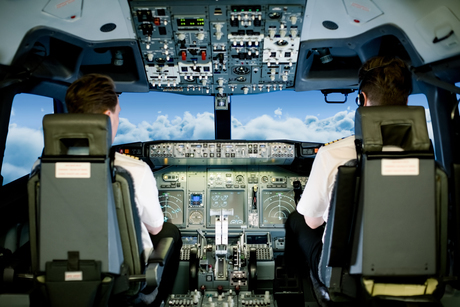 Co pilots sitting on seat in cockpit while flying airplaneの写真素材 [FYI02240008]