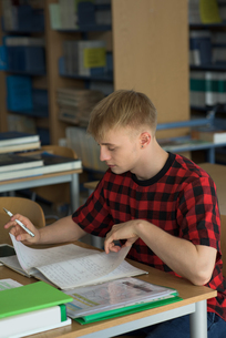 High angle view of young male student studying at deskの写真素材 [FYI02240031]