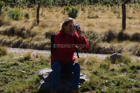 Female hiker photographing while sitting on rockの写真素材 [FYI02240036]