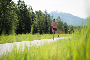 Rear view of woman jogging on roadの写真素材 [FYI02240055]