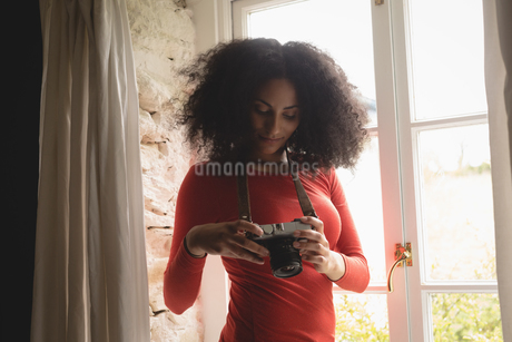 Woman looking at pictures on digital camera at homeの写真素材 [FYI02240083]