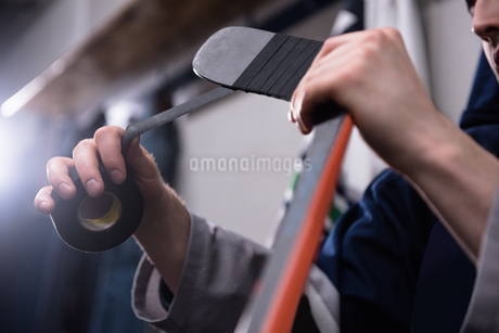 Cropped hands of player taping ice hockey stickの写真素材 [FYI02240103]