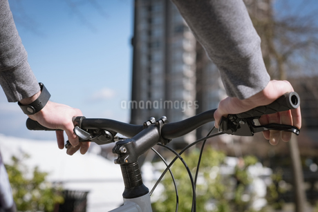 Cropped hands of young man holding bicycleの写真素材 [FYI02240114]