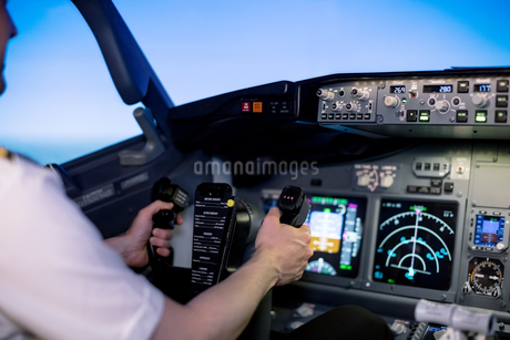 Cropped image of young male pilot holding steering wheel in cockpitの写真素材 [FYI02240163]