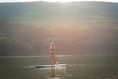 Young woman standing on paddleboard in lakeの写真素材 [FYI02240169]