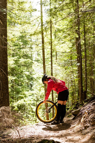 Woman adjusting unicycle while standing on trailの写真素材 [FYI02240181]
