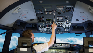 Rear view of young male pilot switching controls in air vehicleの写真素材 [FYI02240185]