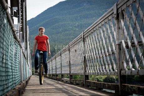 Woman riding unicycle on footbridgeの写真素材 [FYI02240189]