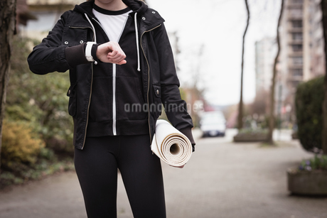 Woman checking time while holding exercise mat in the parkの写真素材 [FYI02240204]