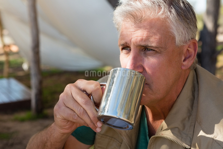 Man drinking coffee at campsiteの写真素材 [FYI02240216]