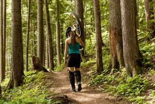 Rear view of woman carrying unicycle on trailの写真素材 [FYI02240222]