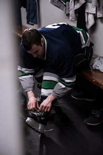 Player tying ice skate in dressing roomの写真素材 [FYI02240237]