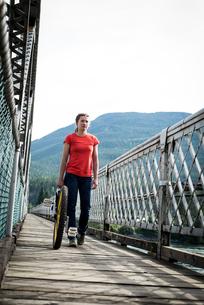Woman with unicycle walking on footbridgeの写真素材 [FYI02240265]