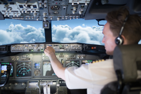Young male pilot wearing headphones switching controls in cockpitの写真素材 [FYI02240297]