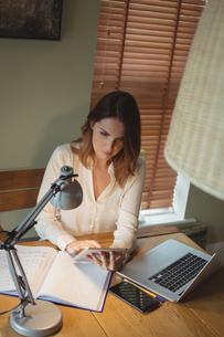 Woman using digital tablet in drawing roomの写真素材 [FYI02240299]