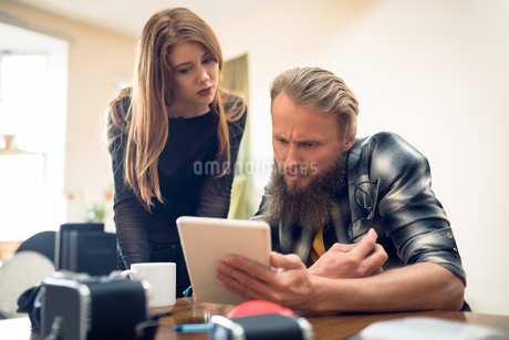 Colleagues looking over digital tablet at deskの写真素材 [FYI02240331]
