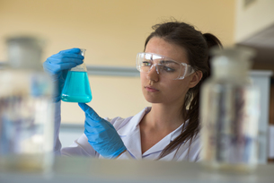 Close up of young female college student looking at chemicalの写真素材 [FYI02240342]