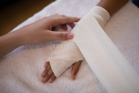 High angle view of female therapist wrapping bandage on hands over white towelの写真素材 [FYI02240345]