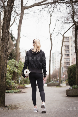 Woman walking with exercise mat in the parkの写真素材 [FYI02240358]