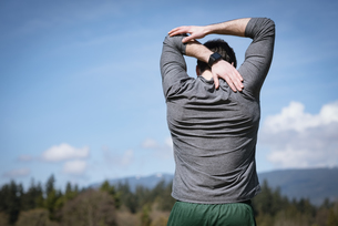 Rear view of man practicing stretching against skyの写真素材 [FYI02240376]