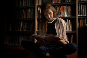 Woman reading book in library roomの写真素材 [FYI02240387]