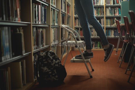 Woman standing in ladder at libraryの写真素材 [FYI02240398]