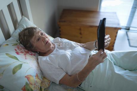 Senior woman using digital tablet on bed in bedroomの写真素材 [FYI02240399]