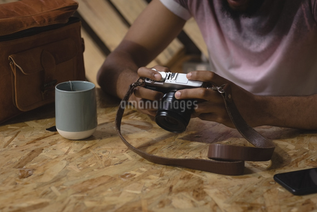 Midsection of young man examining camera in cafeの写真素材 [FYI02240414]