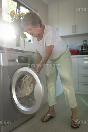 Senior woman putting clothes into washing machineの写真素材 [FYI02240427]