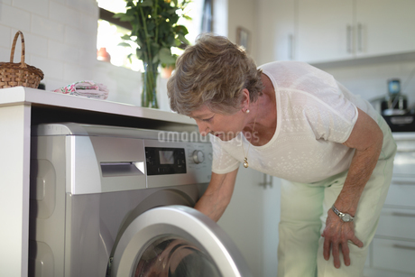 Senior woman putting clothes into washing machineの写真素材 [FYI02240429]