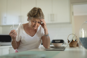 Tense senior woman standing in kitchen with laptop on worktopの写真素材 [FYI02240431]