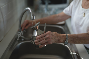 Senior woman filling jug with tap waterの写真素材 [FYI02240443]
