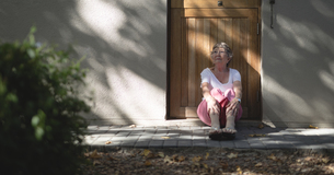 Senior woman sitting outside the door and looking outの写真素材 [FYI02240449]