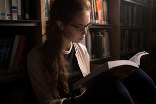Woman reading book in library roomの写真素材 [FYI02240451]