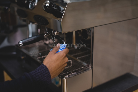 Cropped hand of owner operating coffee makerの写真素材 [FYI02240477]