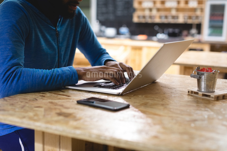 Midsection of young man using laptop in coffee shopの写真素材 [FYI02240482]