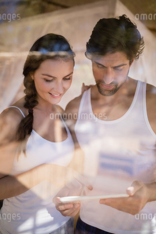 Happy couple using digital tablet in cottageの写真素材 [FYI02240483]