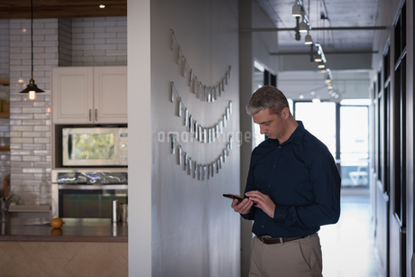Businessman using phone in corridorの写真素材 [FYI02240495]
