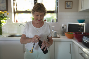 Senior woman removing lid of wine bottleの写真素材 [FYI02240535]