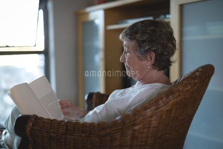 Senior woman reading novel in living roomの写真素材 [FYI02240549]