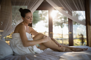 Woman applying lotion while sitting on canopy bedの写真素材 [FYI02240587]