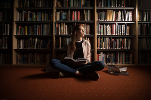 Woman sitting with book in library roomの写真素材 [FYI02240589]
