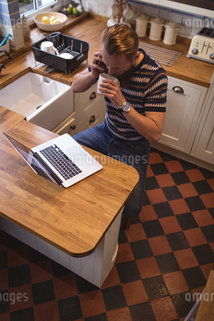 Man talking on phone while having coffee in kitchenの写真素材 [FYI02240595]