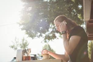 Man talking on mobile phone while having coffeeの写真素材 [FYI02240667]