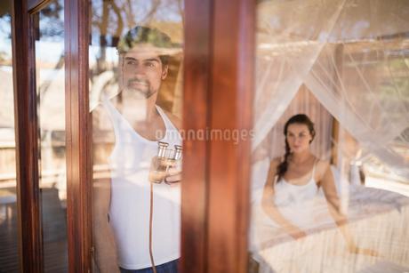 Thoughtful man looking through windowの写真素材 [FYI02240677]