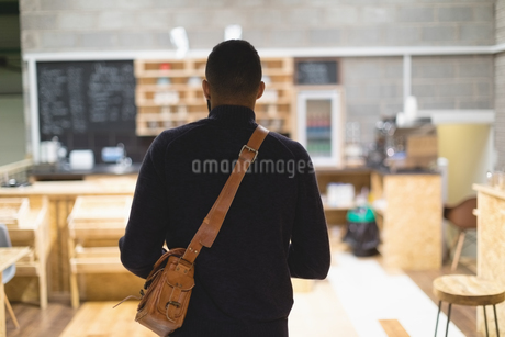Rear view of young man with bag in cafeの写真素材 [FYI02240678]