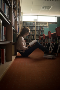 Woman reading book in library roomの写真素材 [FYI02240680]
